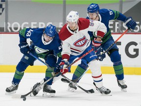 Jan 23, 2021; Vancouver, British Columbia, CAN; Vancouver Canucks defenseman Quinn Hughes (43) and defenseman Tyler Myers (57) check Montreal Canadiens forward Corey Perry (94) in the third period at Rogers Arena. Mandatory Credit: Bob Frid-USA TODAY Sports