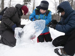 Laudalina Galdamez, left, and Douglas Galdamez help their son Ezequiel complete a whale-shaped ice sculpture, during the St-Lazare winter caravan held at Westwood Junior park on Saturday, Feb. 6, 2021.