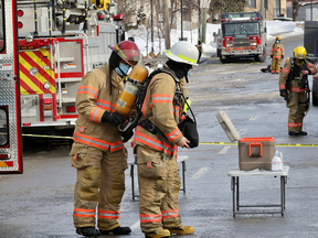 A firefighter has his oxygen tank changed outside an apartment building on Cote-St-Luc Rd. in Montreal Thursday February 18, 2021 after a fire in the building caused traffic problems, power outages and the closing of a school across the street.