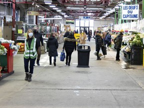 A COVID-19 compliance staffer patrols the retail areas of Jean-Talon Market in Montreal.