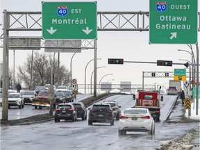 Vehicles and pedestrians pass on St-Jean Blvd. over Highway 40 in Pointe-Claire on Tuesday. Reconstruction of the overpass is scheduled for 2023.