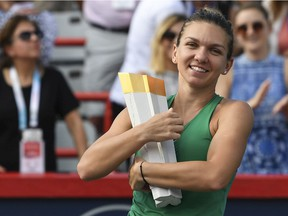 Simona Halep of Romania hugs the Rogers Cup championship trophy after defeating Sloane Stephens in the final at IGA Stadium on Aug. 12, 2018, in Montreal.
