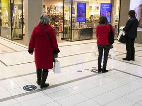 Clients stand in line in front of a cosmetics store in the Champlain Mall in Brossard in December.