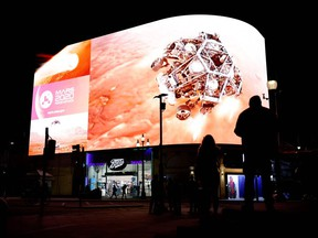 A simulation of the landing of NASA's Perseverance rover on the planet Mars, where it will look for signs of past microbial life, cache rock and soil samples, and prepare for future human exploration, is livestreamed on the Piccadilly Lights screen in central London Feb. 18, 2021.