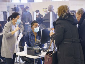 People register to receive their first dose of COVID-19 vaccination in Laval on Thursday, February 25, 2021.