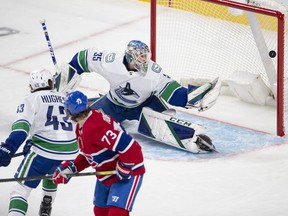Canadiens' Tyler Toffoli deflects the puck past Canucks goaltender Thatcher Demko while defenceman Quinn Hughes watches helplessly Tuesday night at the Bell Centre.
