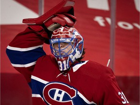 Montreal Canadiens goaltender Carey Price adjusts his mask after drinking water during a break in action against the Ottawa Senators in Montreal on March 2, 2021.