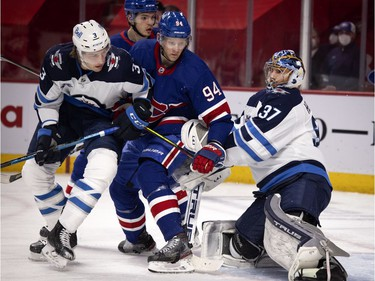 Montreal Canadiens right wing Corey Perry is squeezed between Winnipeg Jets defenseman Tucker Poolman and Winnipeg Jets goaltender Connor Hellebuyck in the first period at the Bell Centre on Thursday, March 4, 2021.