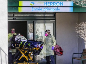 Paramedics wheel a resident out of CHSLD Herron in Dorval on April 8, 2020.