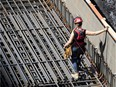 A female construction worker installs rebar on a new condo project in Montreal, on Wednesday, August 12, 2020.