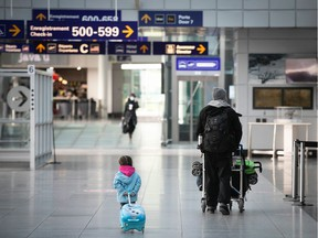 A young traveller follows her father at Montreal Trudeau airport.