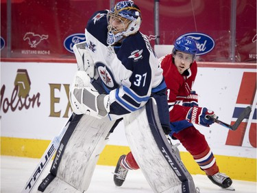 Canadiens' Brendan Gallagher (11) skates past Winnipeg Jets goaltender Connor Hellebuyck behind the net during NHL action in Montreal on Saturday, March 6, 2021.