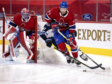 Canadiens defenceman Brett Kulak (77) is pressured by Winnipeg Jets' Nate Thompson (11) as Montreal goaltender Carey Price looks on during NHL action in Montreal on Saturday, March 6, 2021.