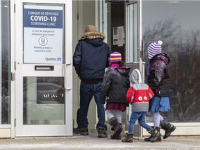 A man enters the COVID-19 testing clinic in Kirkland with three children in March.
