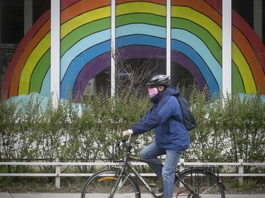 A cyclist wearing a mask rolls by a rainbow on Sherbrooke St. on May 5, 2020.
