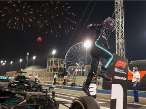 Mercedes' British driver Lewis Hamilton celebrates after winning the Bahrain Formula One Grand Prix at the Bahrain International Circuit in the city of Sakhir on March 28, 2021.