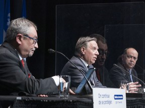 """Premier François Legault responds to a question flanked by Health Minister Christian Dubé, right, and Horacio Arruda, Quebec's director of public health, during a news conference in Montreal, on Wednesday, January 6, 2021. """"Where is the precautionary principle?"""" ask Michel Camus and Nancy Delagrave."""