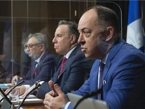Quebec Health Minister Christian Dubé, right, responds to reporters' questions during a news conference on Tuesday, March 23, 2021 at the legislature in Quebec City. Quebec Premier François Legault, centre, and Horacio Arruda, Quebec director of National Public Health, look on.