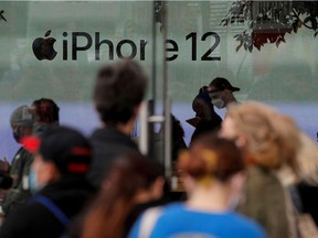 Customers wait in line outside an Apple Store to pick up Apple's new 5G iPhone 12 in Brooklyn, New York, U.S. October 23, 2020.