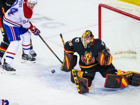 Mar 11, 2021; Calgary, Alberta, CAN; Calgary Flames goaltender Jacob Markstrom (25) makes a save as Montreal Canadiens right wing Corey Perry (94) tries to score during the first period at Scotiabank Saddledome. Mandatory Credit: Sergei Belski-USA TODAY Sports
