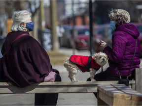 To ward off and to prevent spreading the COVID-19 coronavirus, Anna Fuerstenberg (left) and Lara Shelton, holding her dog Sparky, wear masks outside a café in Montreal Sunday, March 21, 2021.