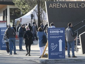 Montrealers wait outside the Bill Durnan arena on Thursday April 8, 2021 for their AstraZeneca vaccine.