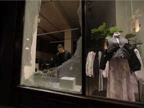 Alex Danino, owner of a clothes store called Rooney Shop in Old Montreal surveys damage made when a crowd gathered to protest an 8 p.m. curfew.