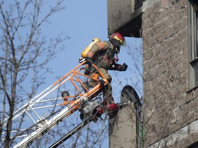 A firefighter climbs from his ladder to the 5th-floor balcony of an apartment during a five-alarm fire at a seniors' residence in Montreal on Sunday, April 11, 2021.