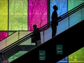 A man riding the escalator up to get his COVID-19 vaccination passes a woman heading down after receiving her shot at the Palais des Congrès in Montreal April 27, 2021.