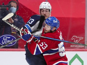 Canadiens' Victor Mete jostles with Jets' Pierre-Luc Dubois during second period at the Bell Centre Thursday night. Mete was benched for the third period in Montreal's 4-2 loss.