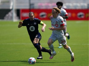 Toronto FC forward Jacob Shaffelburg and CF Montreal midfielder Samuel Piette, left, battle for the ball during the second half at DRV PNK Stadium in Fort Lauderdale, Fla., on April 17, 2021.