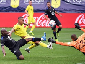 Nashville SC forward Jhonder Cadiz (99) shoots the ball over CF Montréal goalkeeper Clement Diop (23) as he is defended by CFM defender Kamal Miller (3) during the first half  at Nissan Stadium in Nashville, Tenn., on Saturday, April 24, 2021.