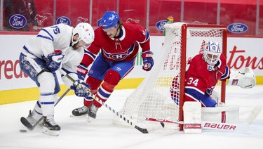 Goalie Jake Allen watches as defenceman Ben Chiarot pokes the puck away from Toronto Maple Leafs' Alexander Kerfoot during second-period action in Montreal on Monday May 3, 2021.