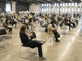 """People sit and after receiving their Pfizer-BioNTech COVID-19 vaccine at the Palais des Congres on Thursday May 13, 2021. """"If you are unwilling to rely on the data from randomized trials, then you can look around and see for yourself what a mass vaccination campaign can accomplish,"""" Christopher Labos writes."""