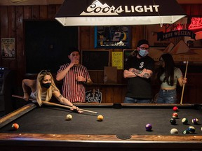 In this file photo taken on Feb. 13, 2021, people wearing masks play pool at Cheswick's West bar in Ocean Beach in San Diego.