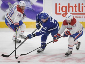 Maple Leafs forward John Tavares (91) tries to skate the puck against Canadiens defenceman Jon Merrill (28) and forward Ryan Suzuki (14) in the first period at Scotiabank Arena in Toronto on Saturday, May 8, 2021.