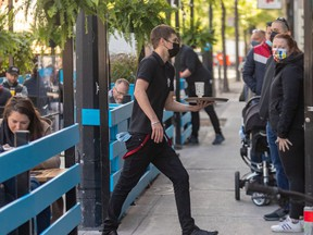 The Burgundy Lion's terrasse is open and full... at 8 a.m. on Friday, May 28, 2021. Waiter Maxime Vatan is busy while more customers wait in line at the Burgundy Lion in Montreal.