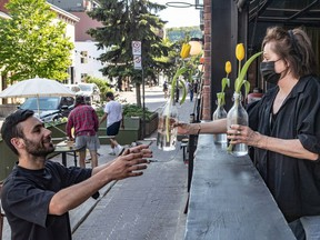 Restaurant La Prunelle owners Annie Tremblay passes flowers to her son, Felix Tremblay in Montreal on Wednesday May 19, 2021.