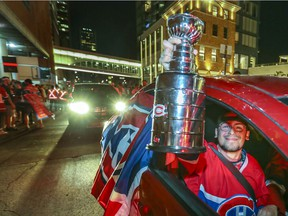 A Montreal Canadiens fan holds a Stanley Cup replica out the car window as his friend drives through throngs of Habs fans outside the Bell Centre after a four-game sweep of the Winnipeg Jets June 7, 2021.