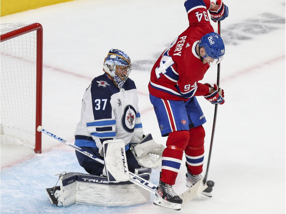 Montreal Canadiens' Corey Perry deflects a shot in front of Winnipeg Jets' Connor Hellebuyck in Montreal on June 7, 2021.