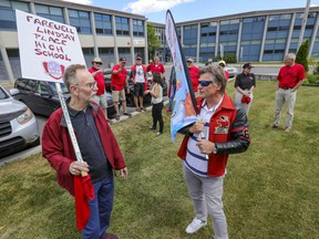 Former Lindsay Place High School teacher Ian Howarth, left, and Peter Bolle, president of the Lindsay Place Alumni Foundation with other former teachers and students outside the school in Pointe-Claire, Wednesday, June 23. Wednesday was the last day of school and last day for the name which will change to St. Thomas High with the relocation of the other English school in Pointe-Claire starting in September.