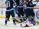 Jake Evans #71 of the Montreal Canadiens lies on the ice injured from a hard check by Mark Scheifele #55 of the Winnipeg Jets after Evans's third-period empty-net goal in Game 1 of the Second Round of the 2021 Stanley Cup Playoffs on June 2, 2021 at Bell MTS Place in Winnipeg.