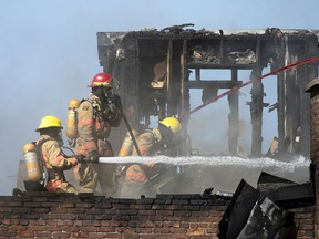Montreal firemen work to put out a blaze on Mont-Royal Ave. in Montreal on Wednesday, June 9, 2021.