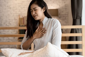Portrait of 20s young Asian woman having difficulty breathing in bedroom at night. Shortness of breath, asthma, difficult to breathe problems