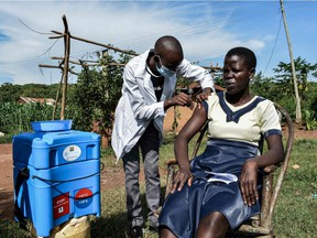 A health worker administers the AstraZeneca vaccine to a woman as part of a door-to-door campaign to deliver the vaccines to people who live far from medical facilities in Siaya, Kenya, on May 18, 2021.