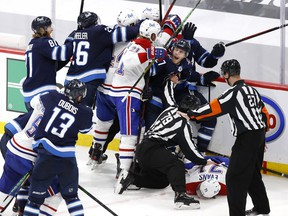 Winnipeg Jets' Nikolaj Ehlers (27) attempts to keep players away from injured Canadiens' Jake Evans (71) after a hit by Jets' Mark Scheifele (not pictured) in Game 1 of the second round of the 2021 Stanley Cup Playoffs at Bell MTS Place in Winnipeg.