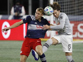 Montreal Impact defender Luis Binks, right, battles New England Revolution forward Adam Buksa for the ball during the first half of MLS match at Gillette Stadium in Foxborough, Mass., on Nov. 20, 2020.