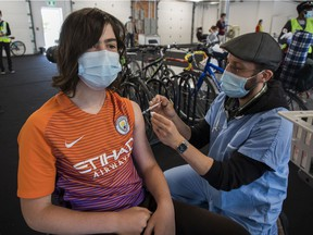 Raphaël Beaudoin gets a COVID-19 vaccine shot from Geoffrey Truchetti at a walk-in (or bicycle ride-in) vaccination centre at the Circuit Gilles Villeneuve in May. Only 16 per cent of Quebecers among those aged 18 to 29 has received two vaccine doses.