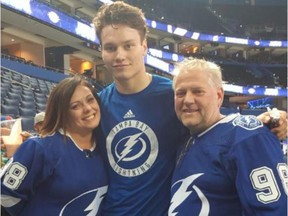 Tampa Bay Lightning defenceman Mikhail Sergachev poses with Michelle and Brian Reid, who were his billet family when he played junior hockey with the OHL's Windsor Spitfires. They taught him to speak English and adjust to life in North America after leaving Russia as a teenager.
