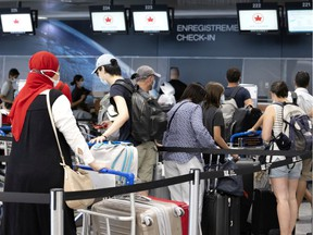 Travellers line up to check in at the Air Canada counter in Trudeau airport in Montreal on Monday, July 19, 2021.